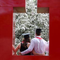 Triplets Sophia Vitale and Ryan Vitale hug while their sister Alex Vitale takes their portrait on the University of Utah's campus before a virtual commencement ceremony on Thursday, April 30, 2020.