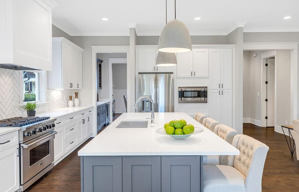 A white kitchen with a huge stove and white island of granite.
