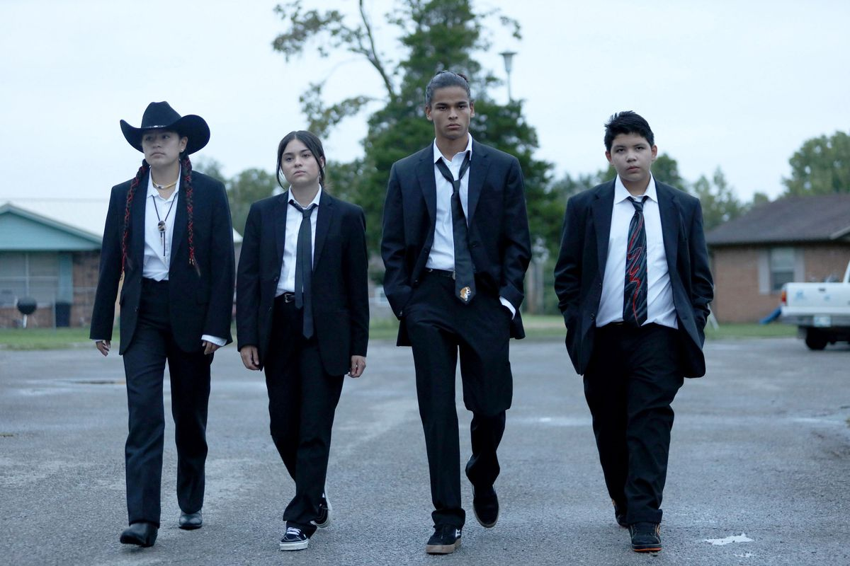 The four main characters of Reservation Dogs walk toward the camera, dressed in snazzy suits.
