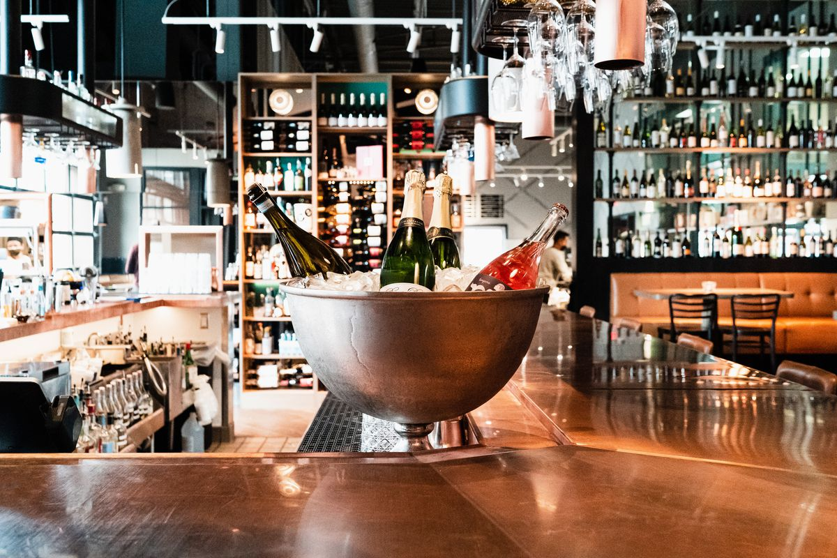 A giant silver bowl on the copper bar filled with ice and bottles of wine