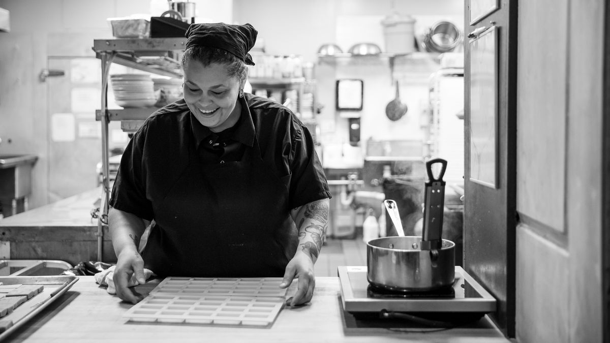 A black and white photo of Monica Greer working at for her previous employer Lady of the House, in the kitchen.