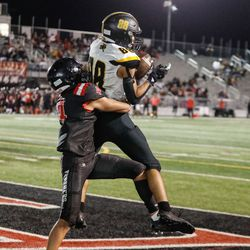 Roy's Jesse Dockery (88) catches a touchdown as West's Daniel Aneo defends as they compete in a high school football game Friday, Sept. 10, 2021, at West High School in Salt Lake City.