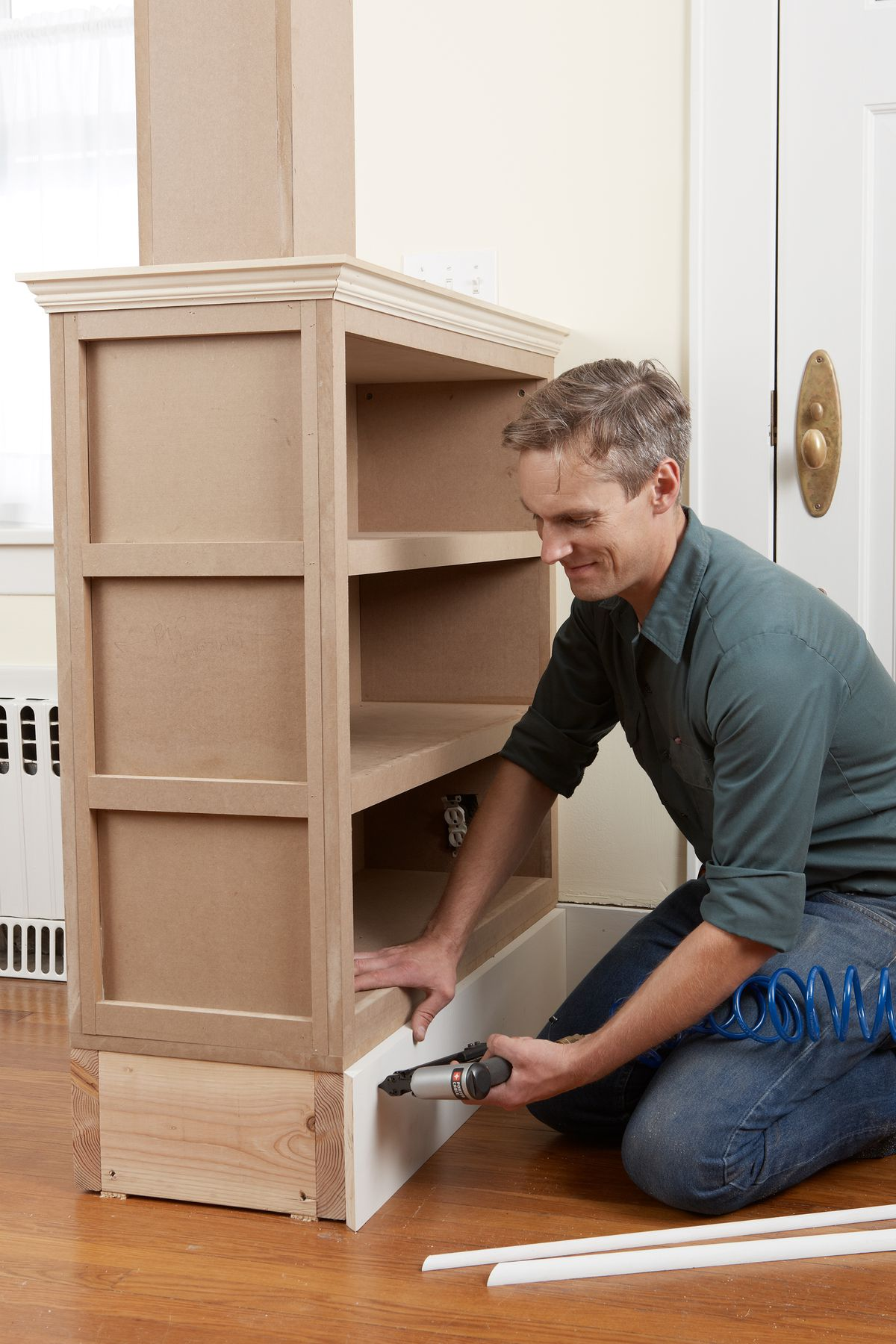 Man Installs Baseboard Molding Of Room Partition