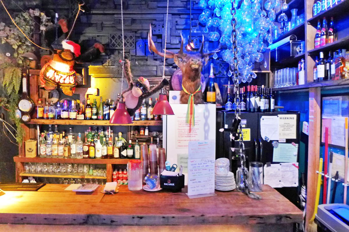 A wooden bar has gorilla stuffed animals hanging above it, and an animal head and liquor bottles behind it