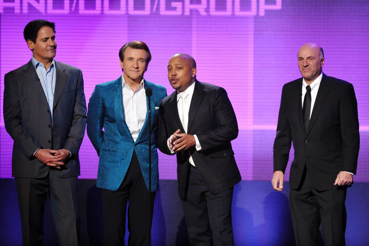 """From left, Mark Cuban, Robert Herjavec, Daymond John and Kevin O'Leary, of """"Shark Tank,"""" present the award for favorite band, duo or group - pop rock at the American Music Awards at the Nokia Theatre L.A. Live on Sunday, Nov. 24, 2013, in Los Angeles. John is being accused of price gouging important medical supplies."""