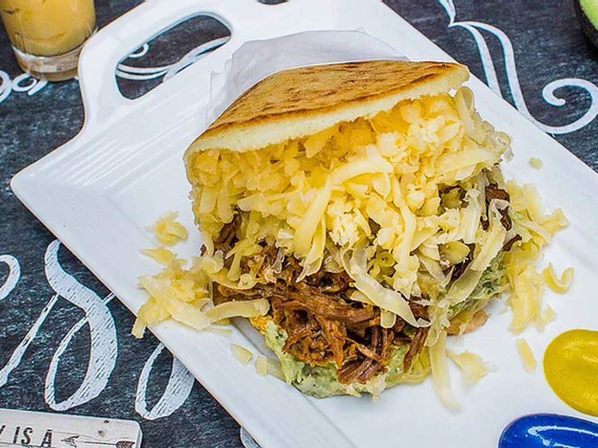 An arepa filed with meat, cheese, and veggies.