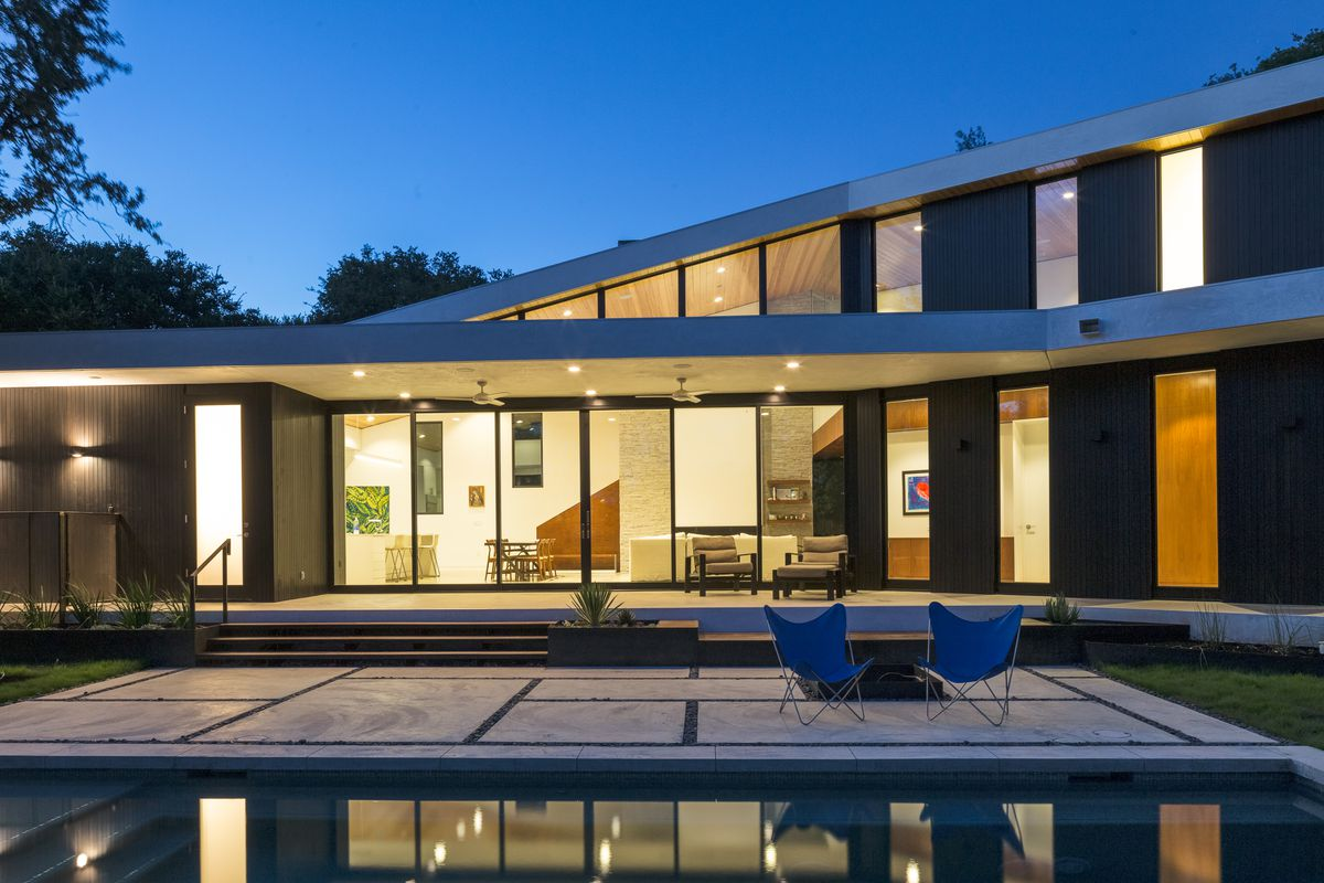 exterior of modernist contemporary house with lights on inside at dusk including large patio and pool