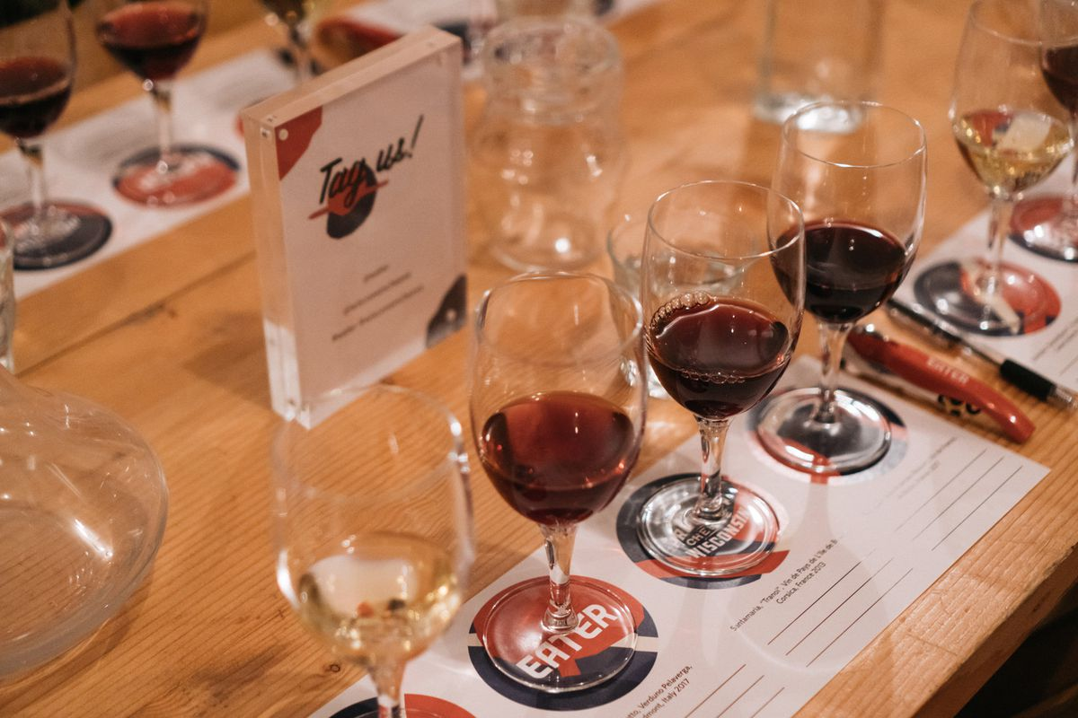 Glasses of wine organized on an Eater-branded placemat.
