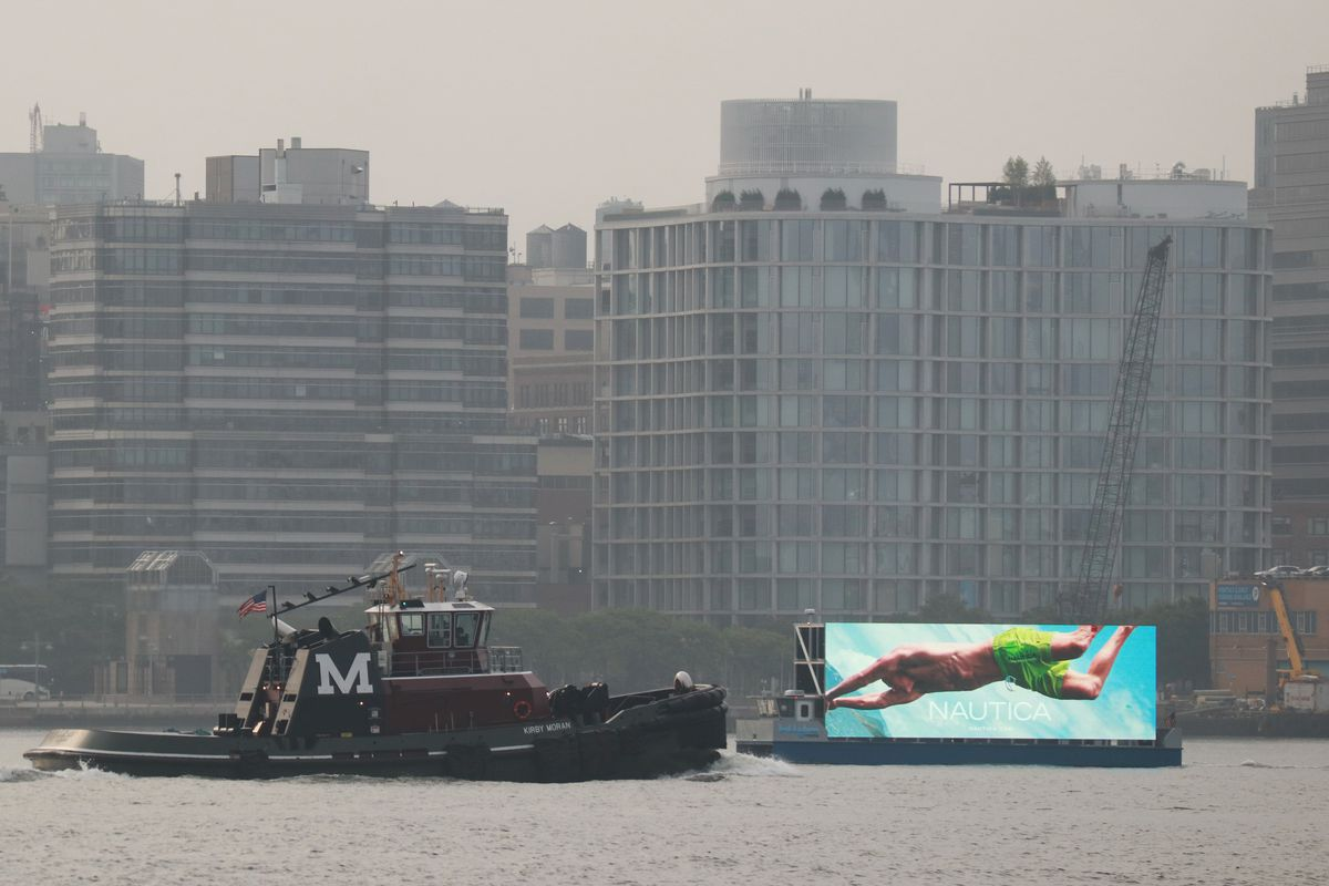 A digital billboard barge on the Hudson River advertising the Nautica clothing brand.
