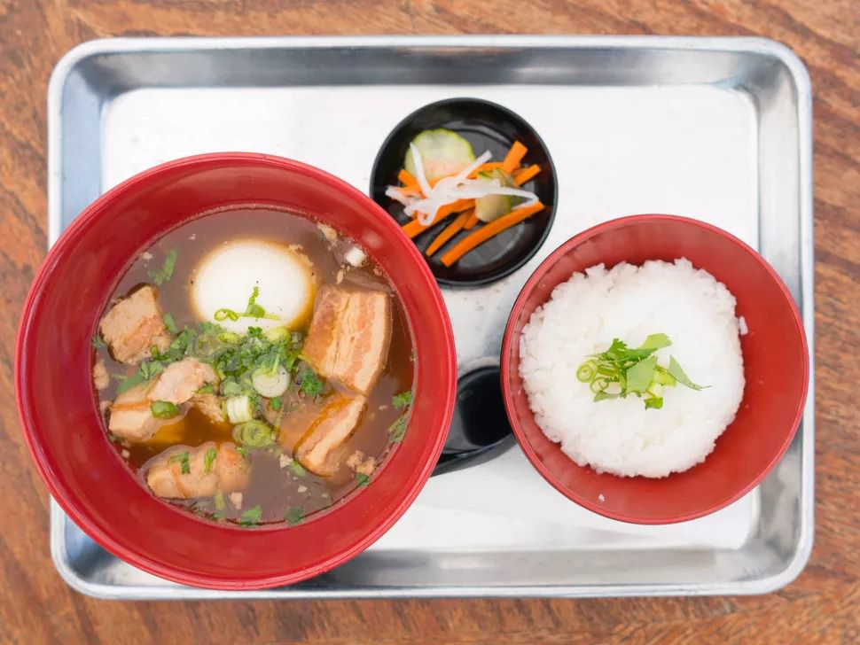 A picture of a red bowl of caramelized pork belly in a broth with a whole soft-boiled egg, with a side of rice and some pickles
