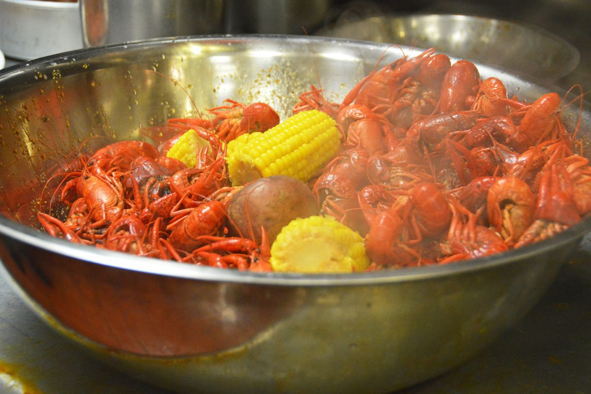 A silver bowl filled with boiled crawfish and corn