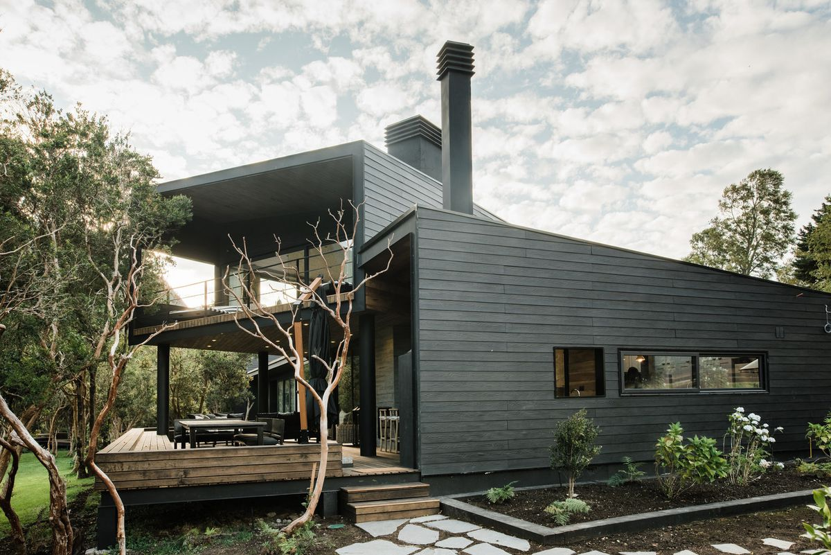 Exterior of black clad house with a second level with deck.