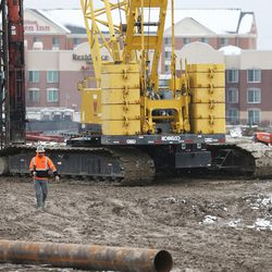 A worker walks in the mud at the construction site of the new Mountain America Credit Union Corporate offices in Sandy. Commercial construction in Sandy and Lehi on Wednesday, Dec. 21, 2016.
