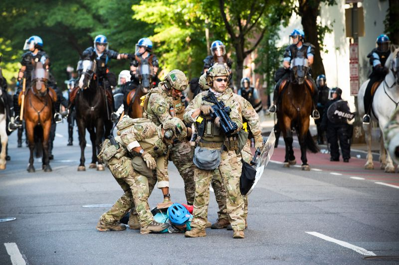 Three troops in camouflage, in armor and holding weapons, pin a person wearing a blue bike helmet to the ground as mounted police look on.