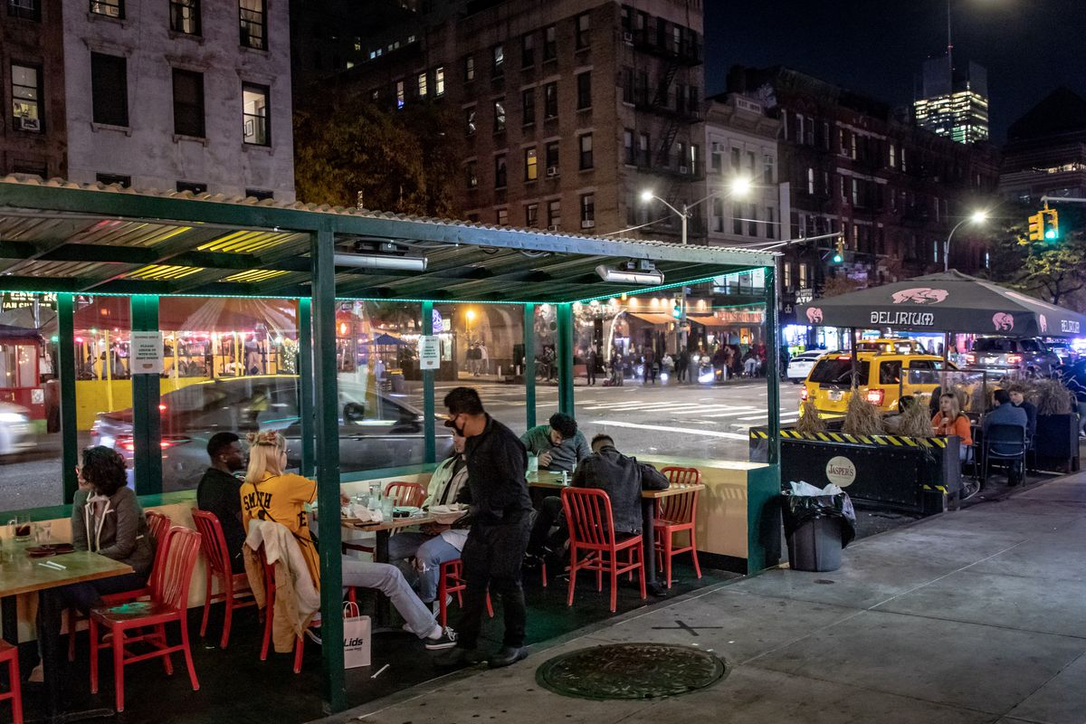 Patrons gather under a streetside green patio underneath an awning on Ninth Avenue