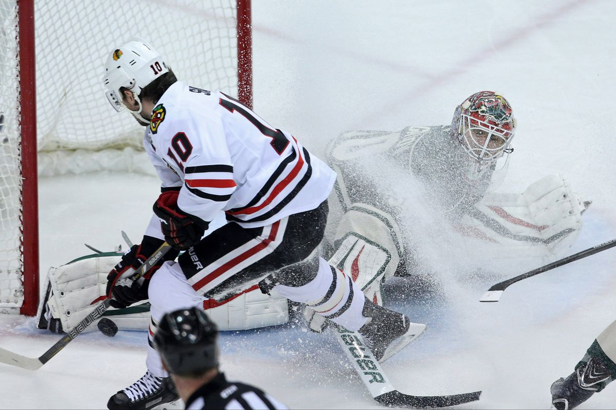 Minnesota Wild goaltender Ilya Bryzgalov makes a stop on Chicago Blackhawks forward Patrick Sharp.