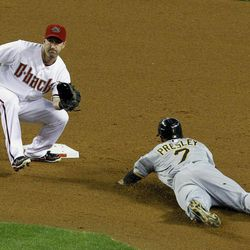 Arizona Diamondbacks' Willie Bloomquist, left, gets ready to catch the ball before tagging out a sliding Pittsburgh Pirates' Alex Presley, as he attempted to steal second base, during the fifth inning in an MLB baseball game Monday, April 16, 2012, in Phoenix.  The Diamondbacks defeated the Pirates 5-1.