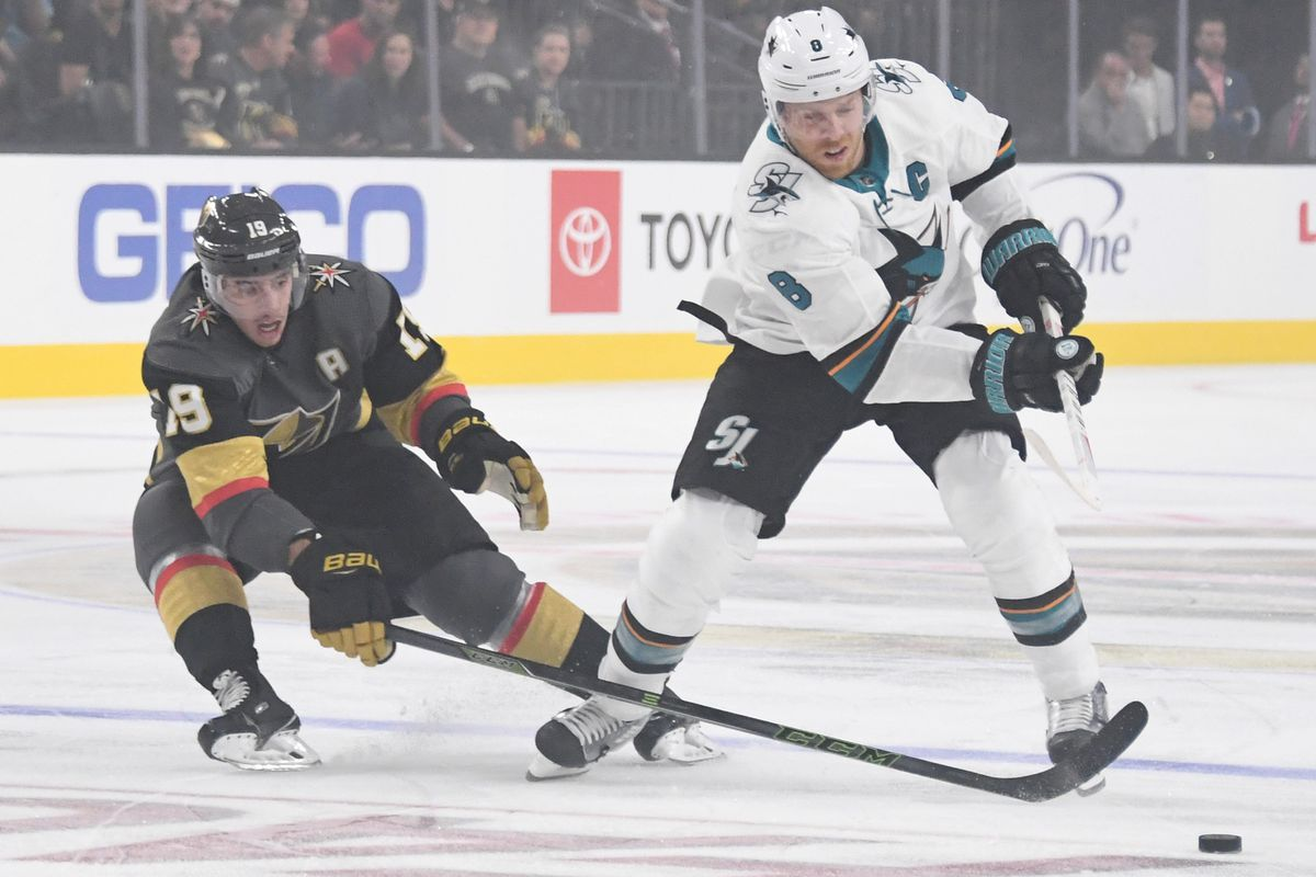 LAS VEGAS, NEVADA - SEPTEMBER 30: Reilly Smith #19 of the Vegas Golden Knights pokes the puck away from Joe Pavelski #8 of the San Jose Sharks in the first period of their preseason game at T-Mobile Arena on September 30, 2018 in Las Vegas, Nevada.
