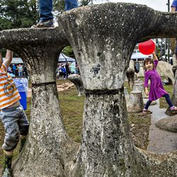 Isaac Hurley (left) climbs the stone artwork in Cabbagetown Park during Chomp & Stomp.