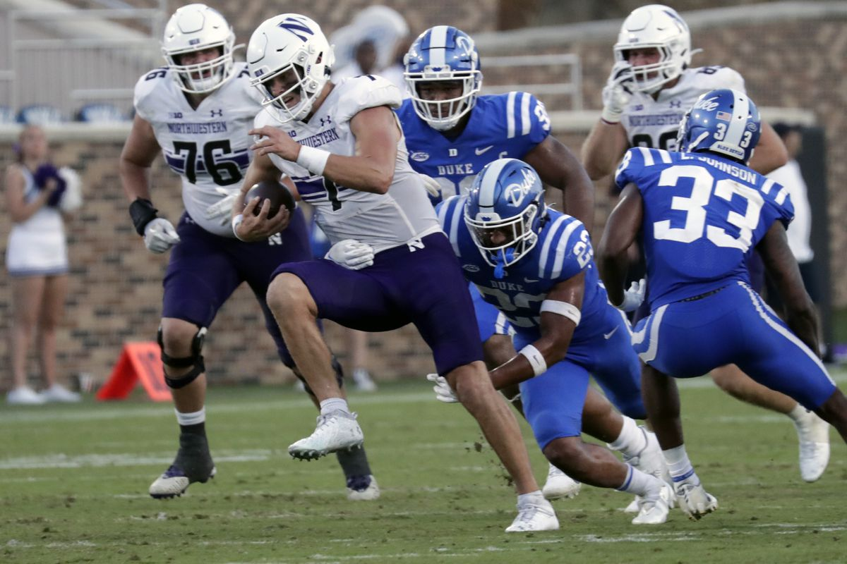 Northwestern quarterback Andrew Marty (7) evades Duke safety Lummie Young IV (23) on a run during the second half of a game Sept. 18.