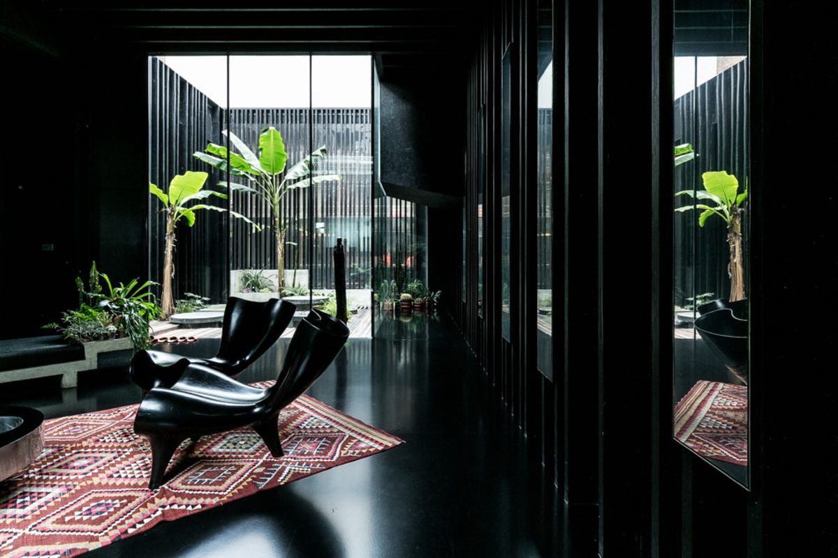 Interior shot of a living area painted completely black illuminated by a glazed courtyard.