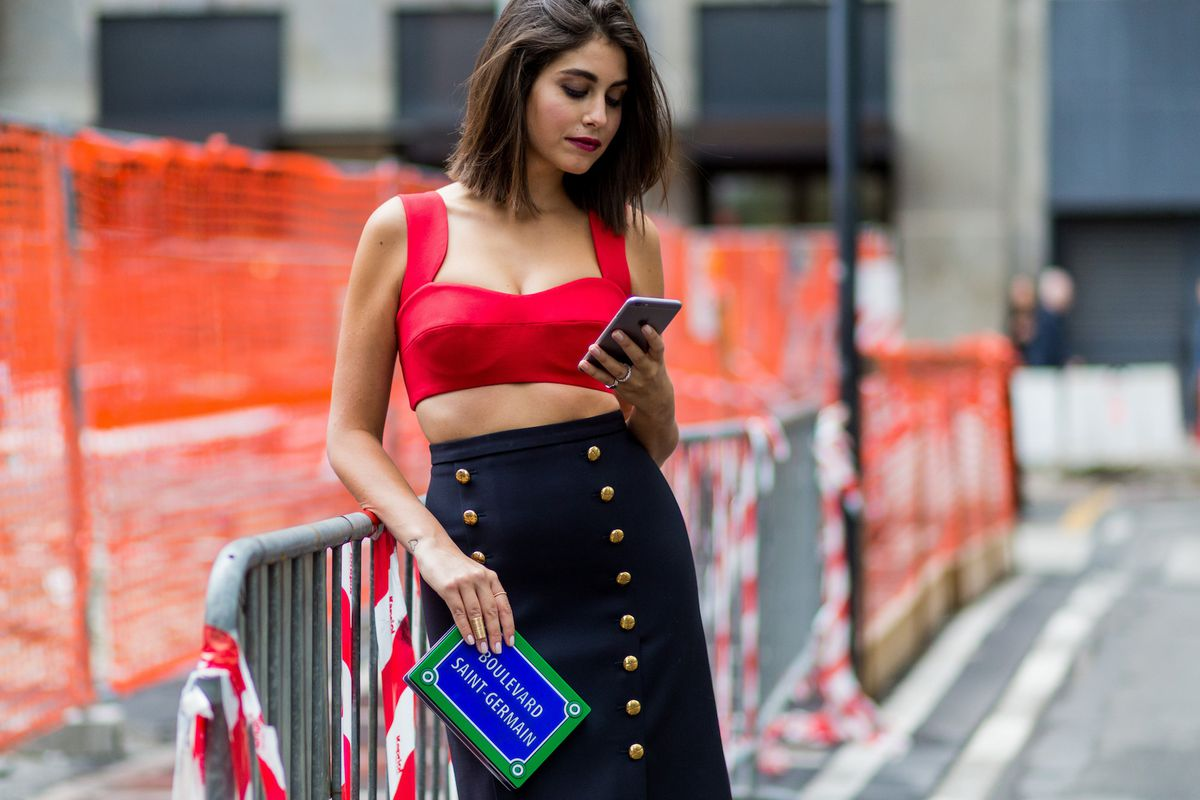 A blogger on her cell phone standing on the street and holding a clutch