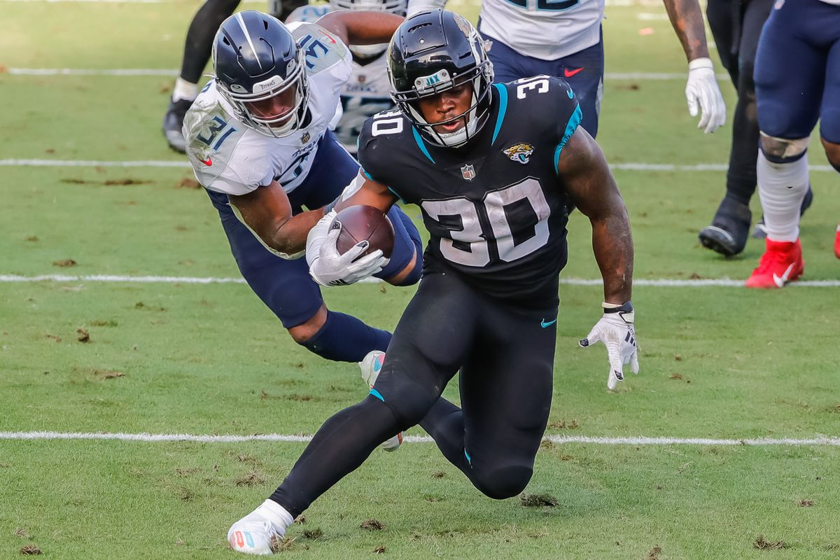Jacksonville Jaguars running back James Robinson (30) carries the ball past Tennessee Titans free safety Kevin Byard (31) during the second half at TIAA Bank Field.