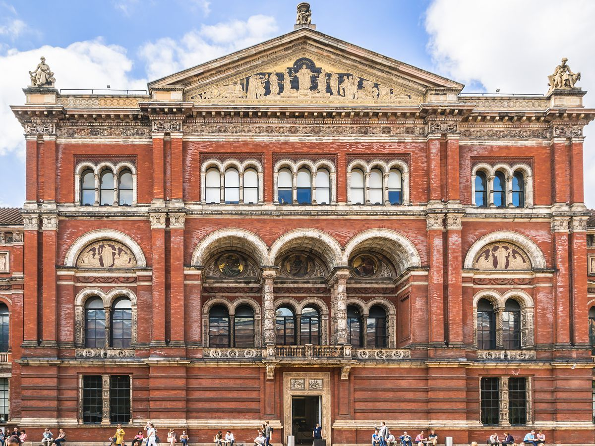 The exterior of the Victoria and Albert Museum in London. The facade is red brick and there are archways over the entrance area.