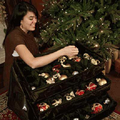 Person placing Christmas ornaments neatly in an ornament chest.