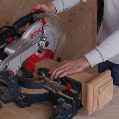 Person using a miter saw to cut the newel post on a DIY poker table.