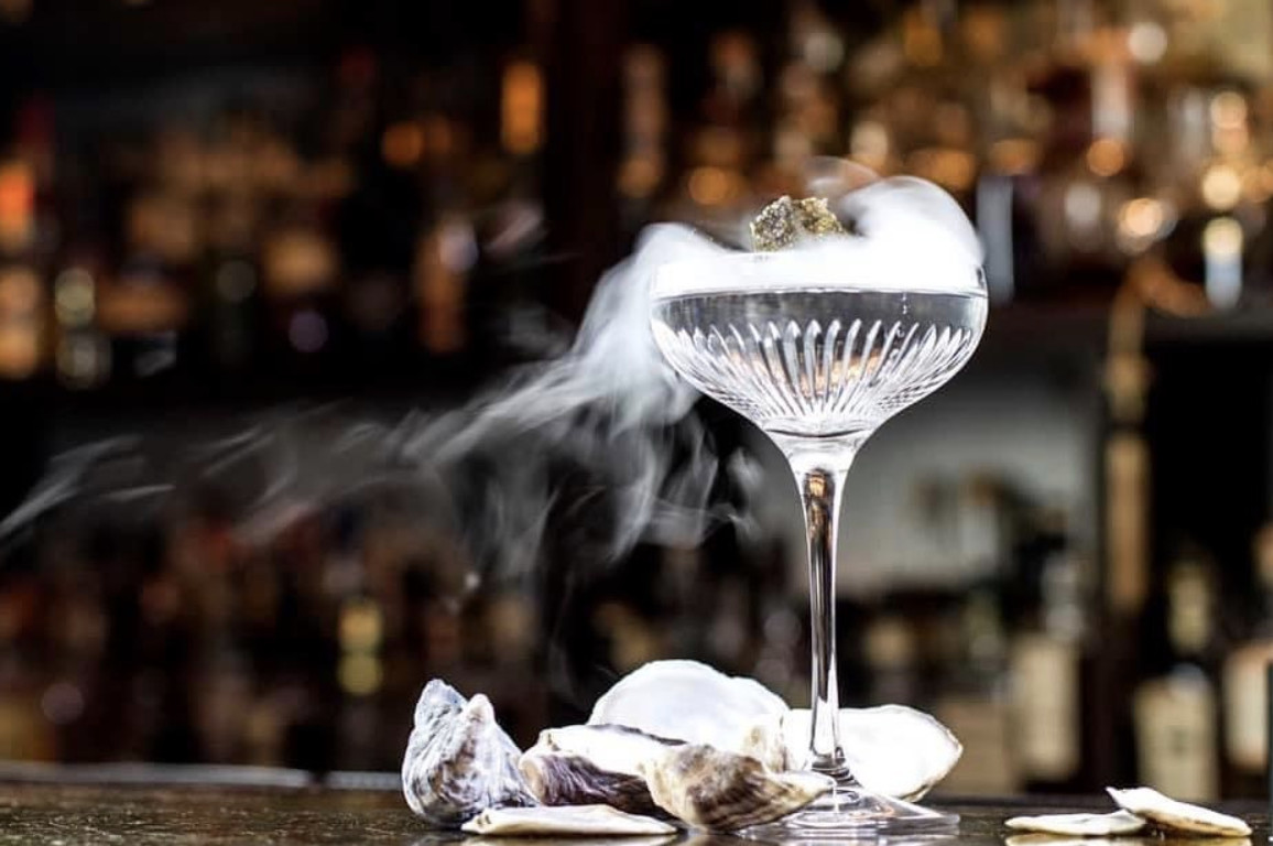 A martini on a bar with smoke rising from the glass
