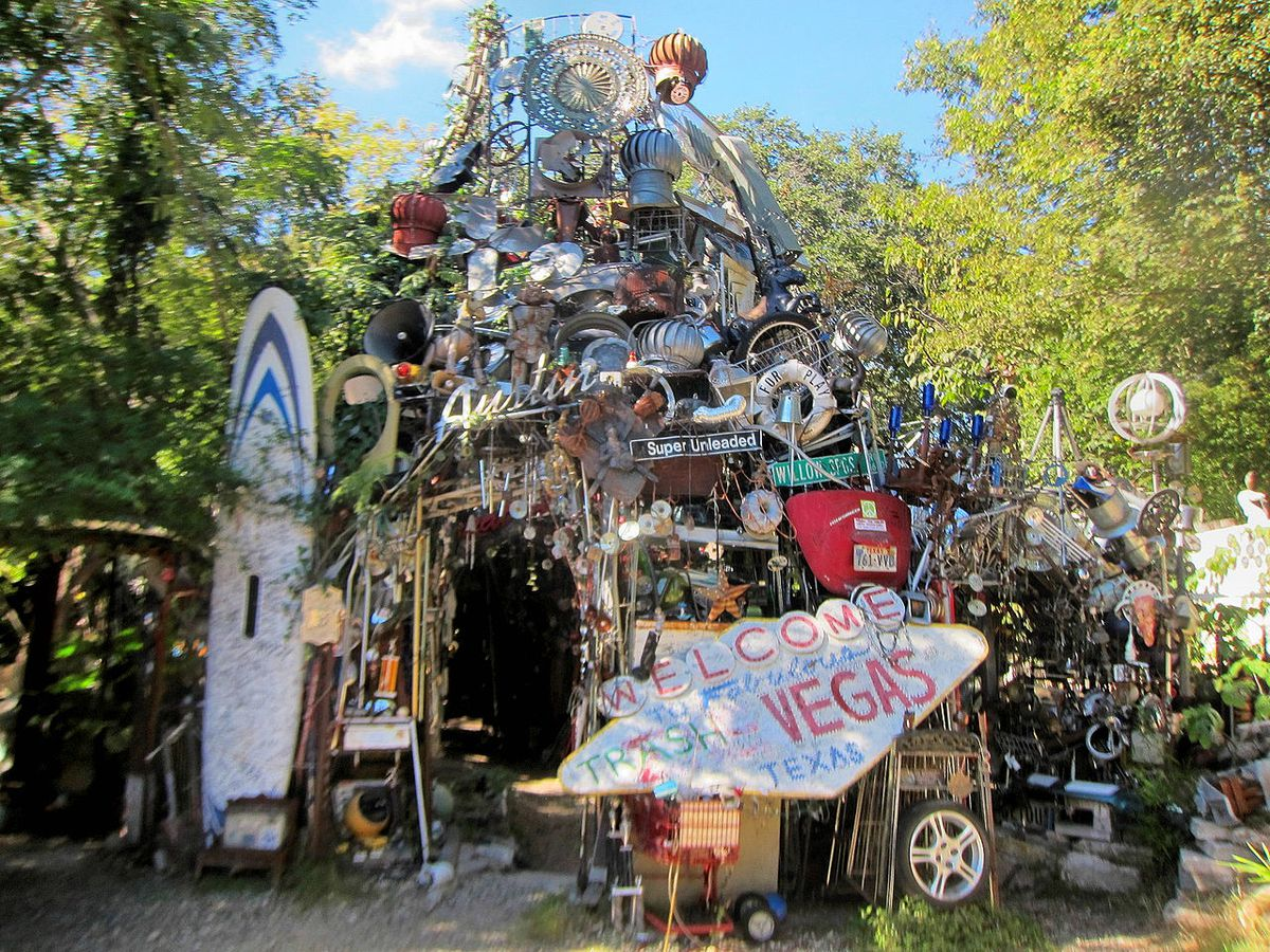 A tower made of various colorful castoff metal, plastic, and other items, outdoors, with trees in back.