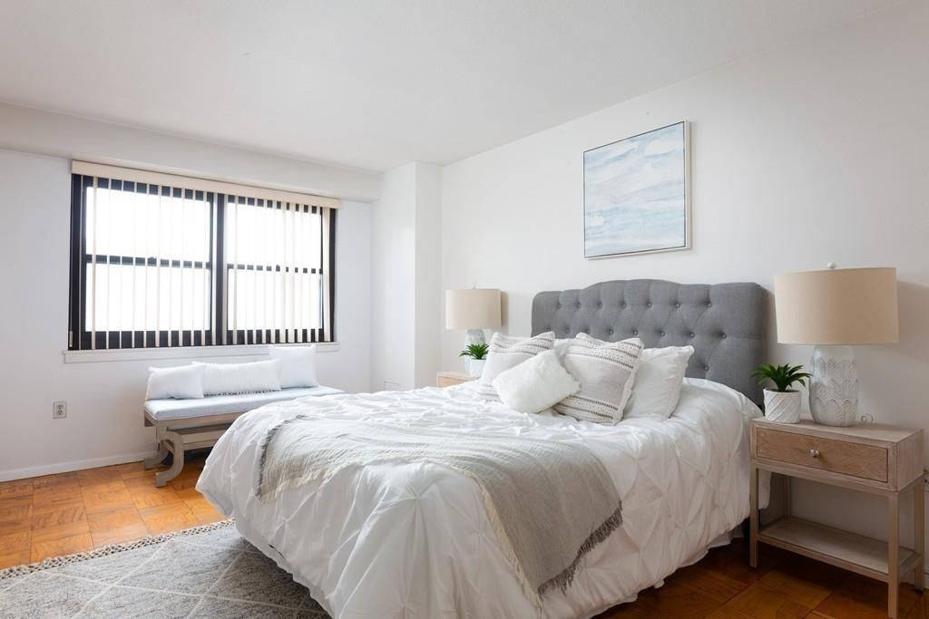A bedroom with a bed and two windows.