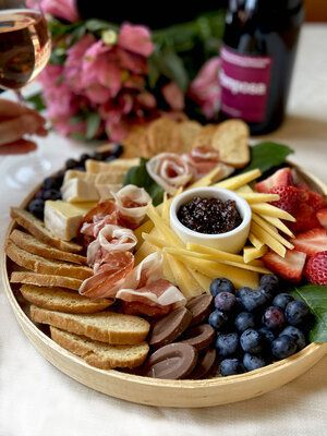 A charcuterie plate of fruit, meats, and cheeses.