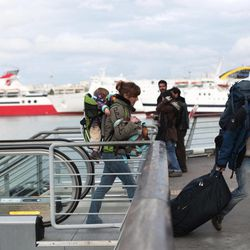 Tourists carry their baggage as in the background are seen docked ships during a 48-hours strike at the port of Piraeus, near Athens, on Tuesday, April 10, 2012. Ferry services to Greek islands have been halted by a 48-hour strike that is expected to hit the start of the country's tourism season and celebrations for Orthodox Easter this Sunday.