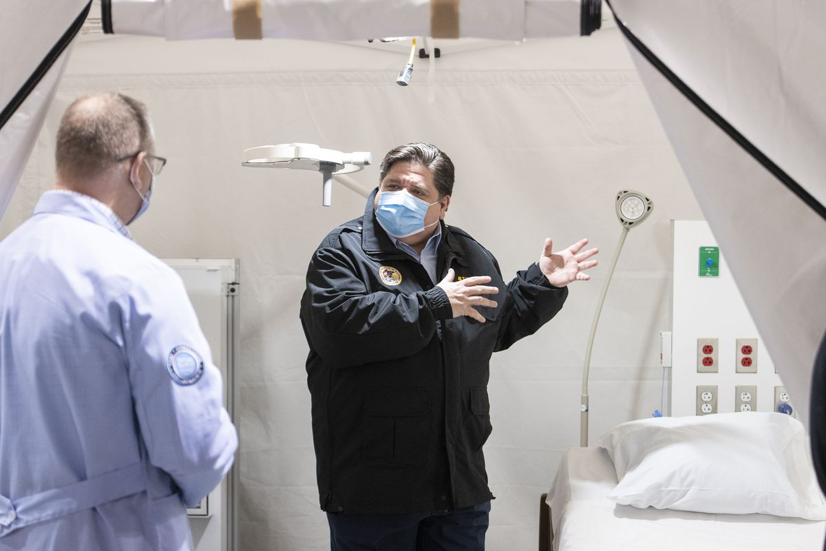 Governor J.B. Pritzker, wearing a windbreaker and a blue mask, speaks with health care worker in a white COVID treatment room.