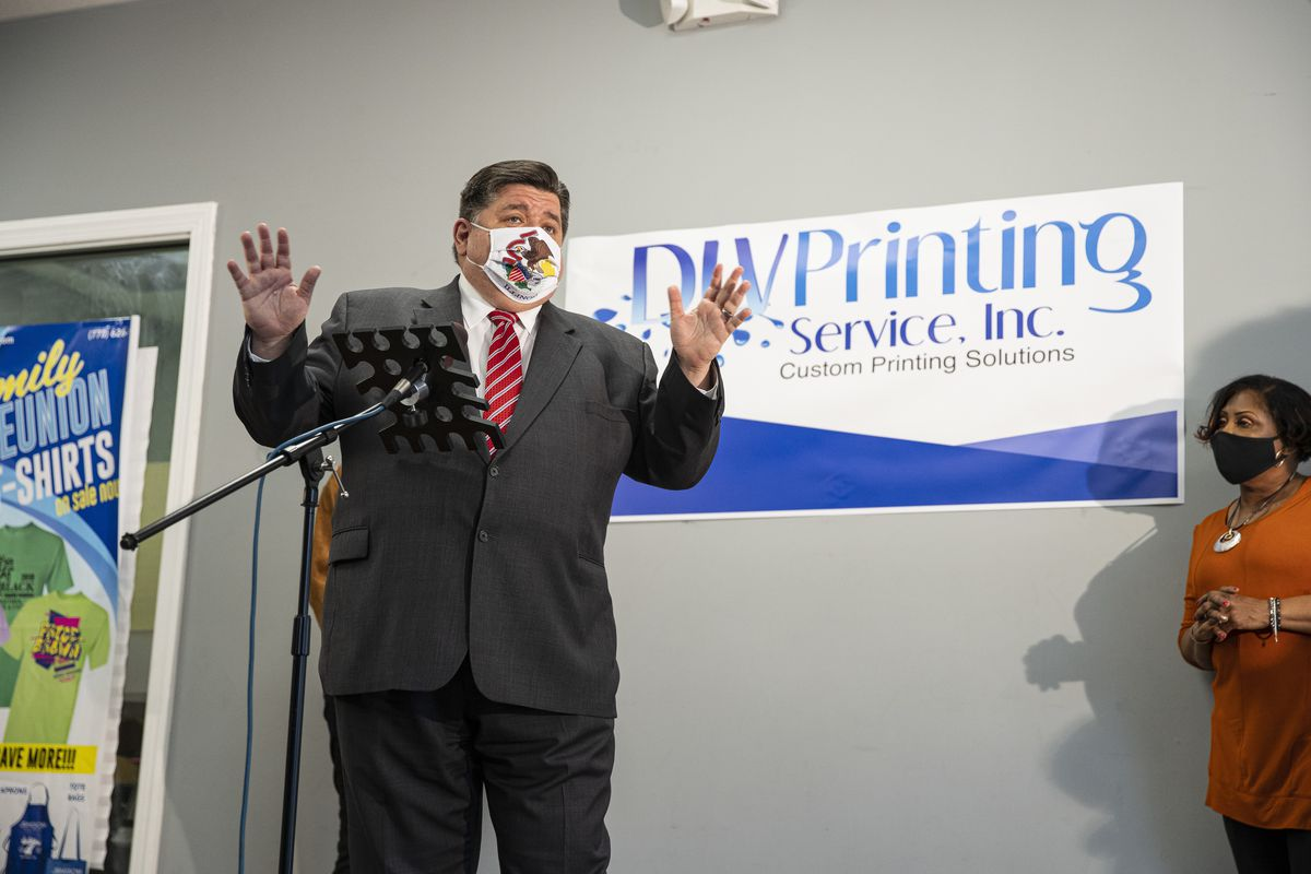 Gov. J.B. Pritzker answers questions from the media in the South Austin neighborhood on  Wednesday.