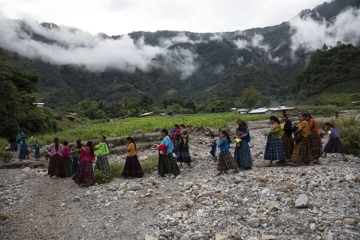 After a church service, women and children walk to a communal meeting to discuss problems regarding housing and donations received by the international community.