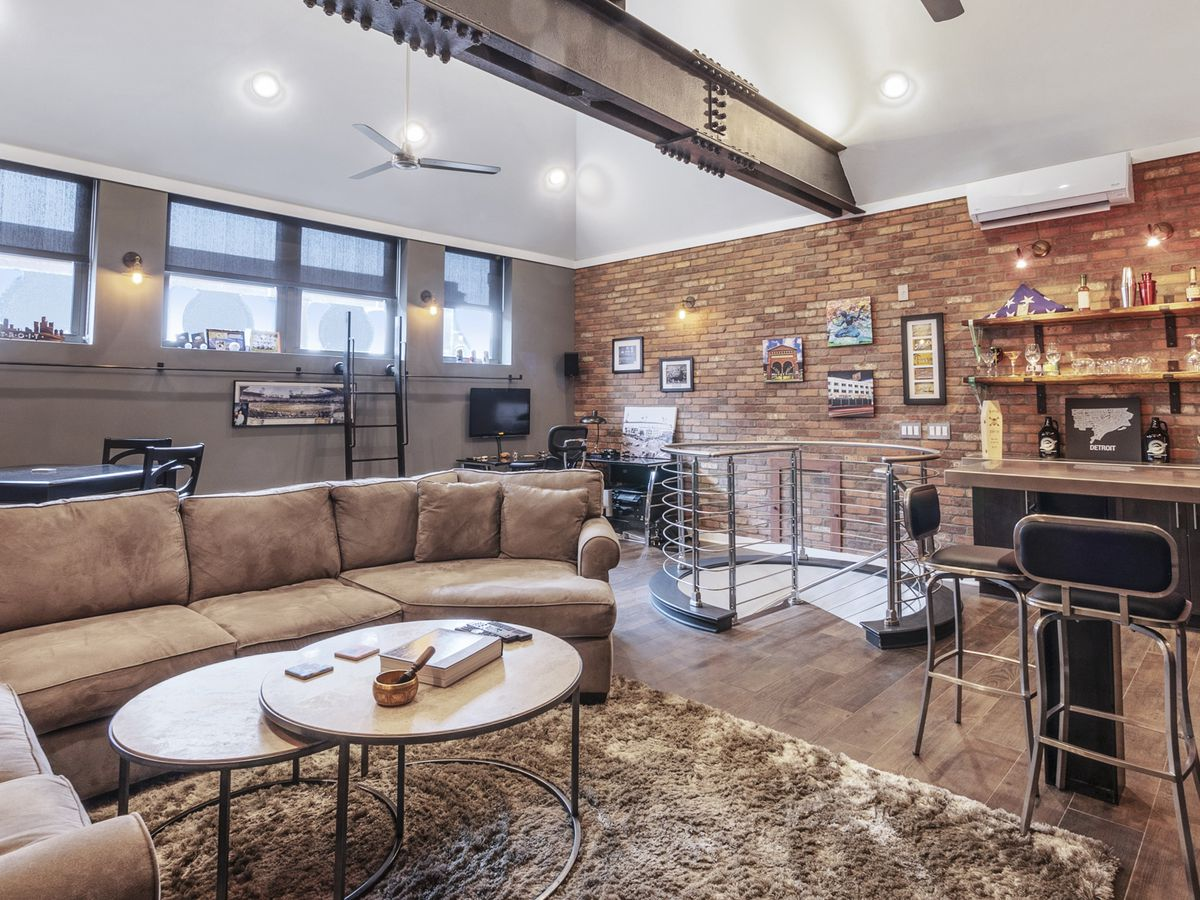 Second-story loft with exposed brick and bar.