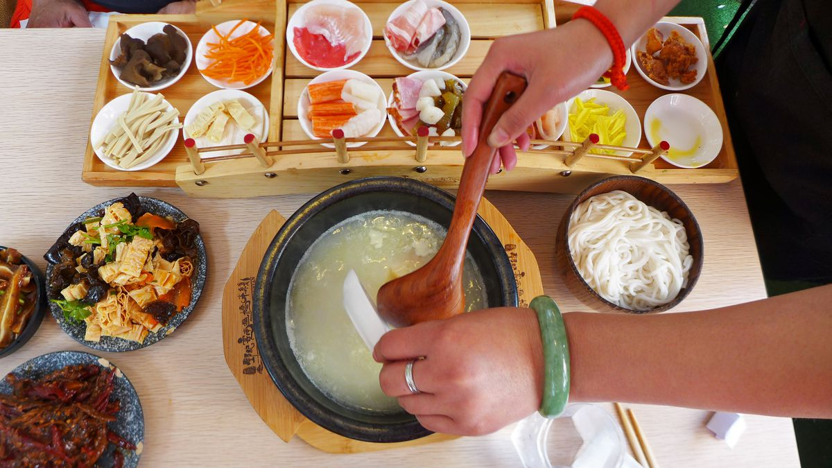 A bunch of tiny white bowls filled with things on a wooden bridge, as a disembodies arm dumps them in a noodle soup.