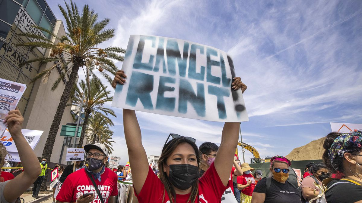 """A person in a group of protesters holds a sign over their head that reads, """"Cancel rent!"""""""