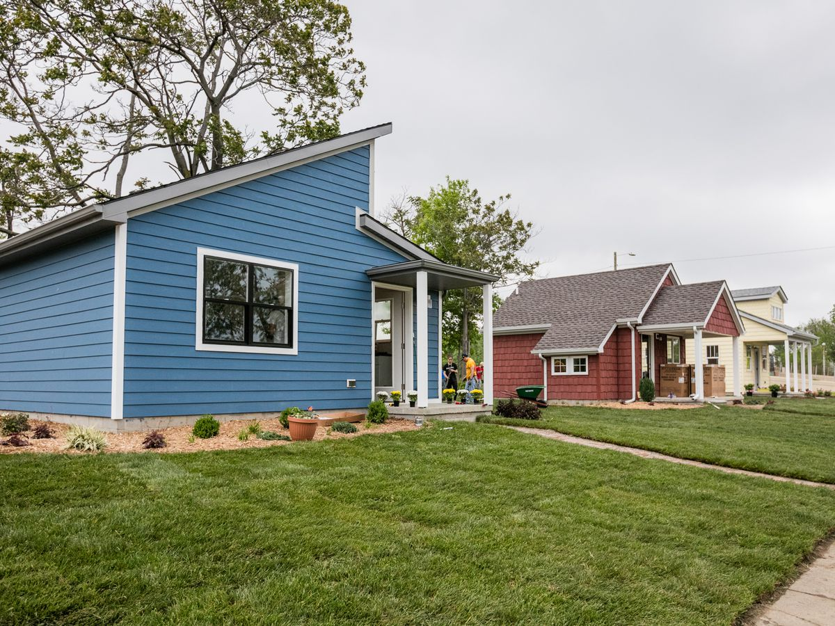 Three small single-story homes, colored blue, red, and white, sit in a row behind well-mowed lawns.