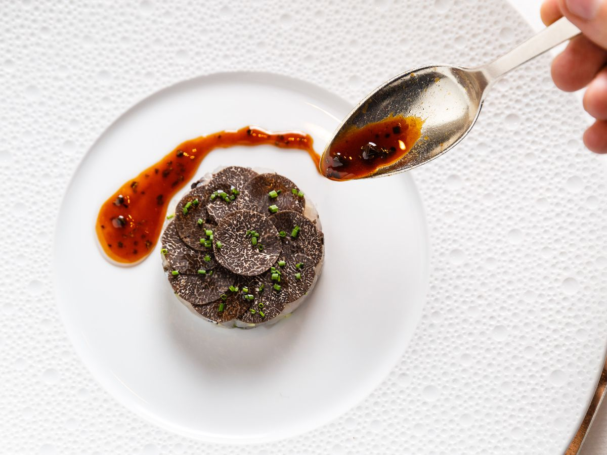 Round circles of black truffle sit atop striped bass tartare, while a waiter sauces the white plate with Perigord vinaigrette