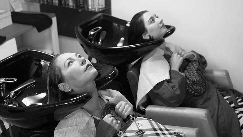 A mother and a daughter sit with their heads in salon hair-washing tubs.