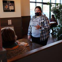 Server Cassie Lambert talks with customers at Oak Wood Fire Kitchen in Draper on Tuesday, Dec. 8, 2020.