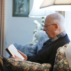 Roger Thompson, 99, reads at his home in Salt Lake City Friday, Dec. 3, 2013.