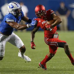 Utah Utes running back Troy McCormick Jr. (4) is brought down by Brigham Young Cougars linebacker Fred Warner (4)  in Provo on Saturday, Sept. 9, 2017.