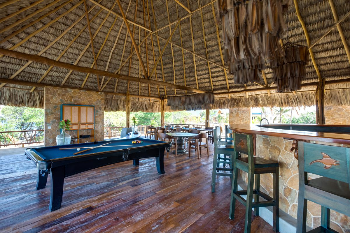An open air common area under a thatched roof contains a pool table and bar with seating on a private island in Belize.