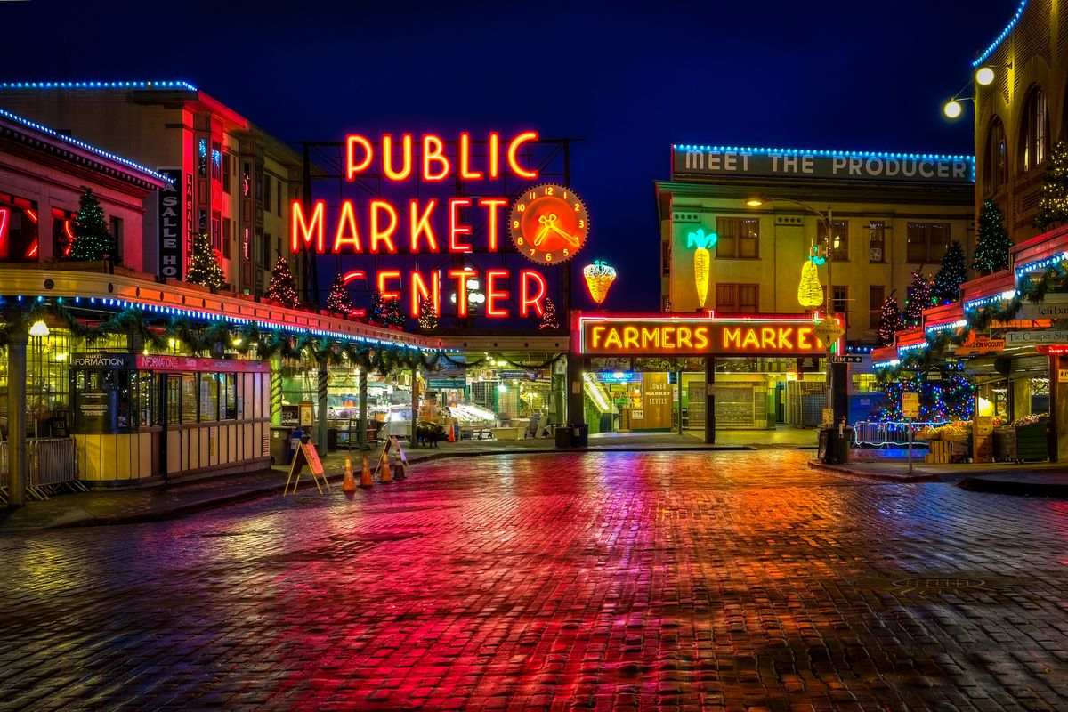The exterior of Pike Place Market with the iconic neon sign lit up at night above rain-slicked cobblestone streets