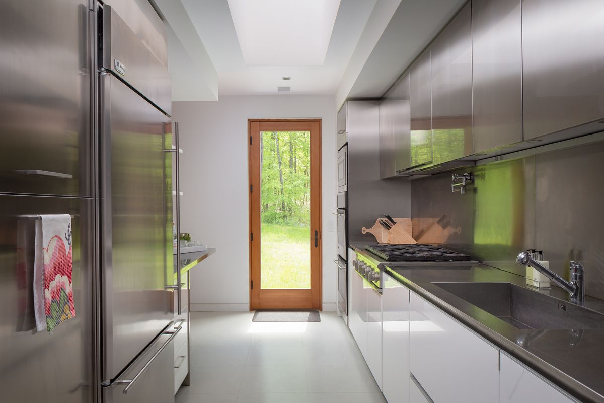 A galley style kitchen has white cabinets and stainless steel countertops and upper cabinets.